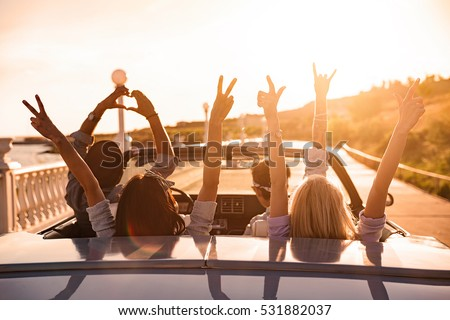 Group of happy young friends in cabriolet with raised hands driving on sunset #531882037