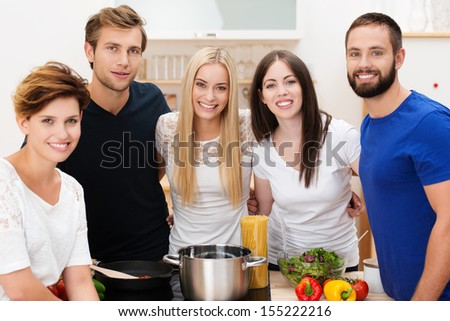 Group of happy young friends preparing lunch standing smiling at the camera grouped around the stainless steel pot and fresh healthy ingredients