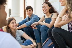 Group of happy young friends sitting in college campus and talking. Cheerful group of  smiling girls and guys feeling relaxed after university exam. Excited millenials laughing and having fun outdoor.