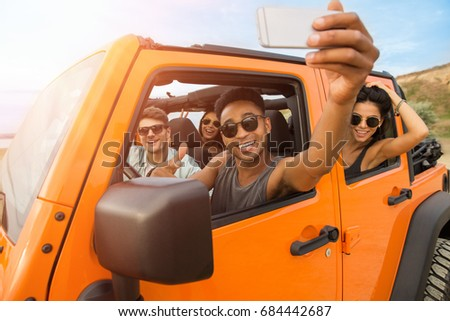 Group of happy young friends taking a selfie while sitting in a convertible car outdoors