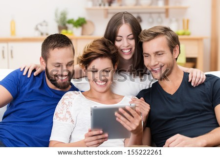 Group of happy young men and women sitting on a sofa together sharing a tablet computer and reading information on the screen