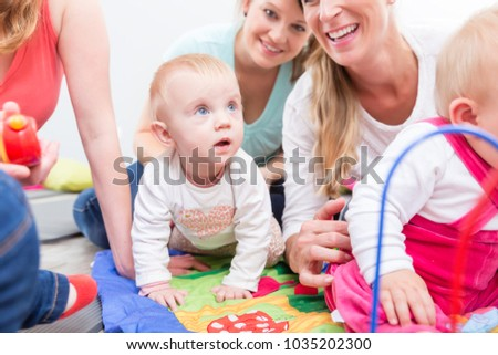Group of happy young mothers watching their cute and healthy babies while playing with multicolored toys in a modern daycare center