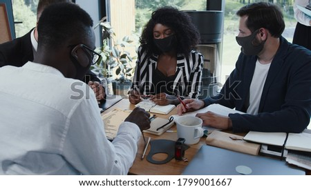 Group of happy young multiethnic business people wearing masks working at office table. Safe workplace after COVID-19.