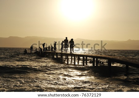 Group of happy young people at the beach on beautiful summer sunset walking on breakwater - stock photo
