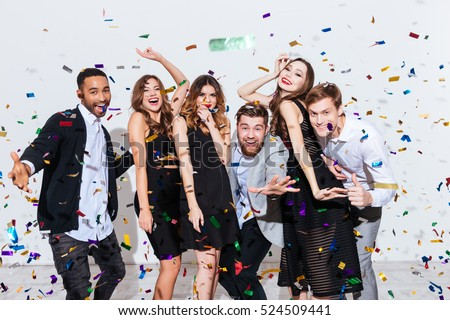 Group of happy young people celebrating and having fun together over white background