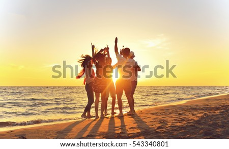group of happy young people dancing at the beach on beautiful summer sunset #543340801