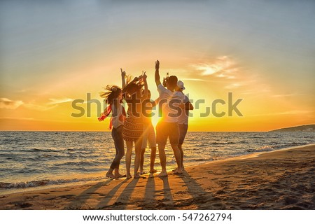 group of happy young people dancing at the beach on beautiful summer sunset #547262794