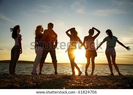 group of happy young people dancing at the beach on  beautiful summer sunset #61824706