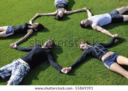 group of happy young people lie on grass outdoor at sunny day