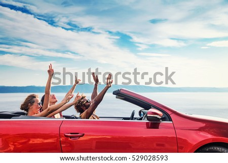 Group of happy young people raising hands to the air in the red convertible. #529028593