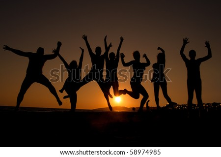 group of happy young people silhouettes jumping on the beach   on beautiful summer sunset - stock photo