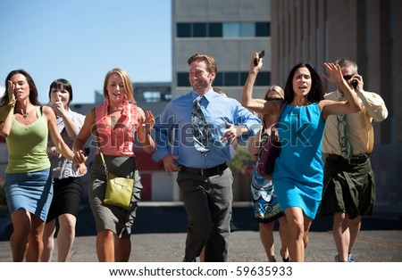 Group of hard working business men and women run down city street.