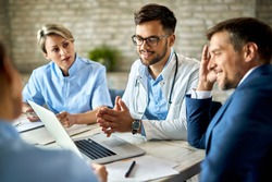 Group of healthcare workers and businessman using laptop while having a meeting in the office. Focus is on young doctor.