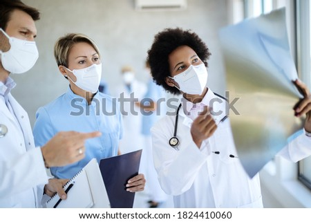 Group of healthcare workers examining X-ray image at hospital hallway. They are wearing protective face masks due to COVID-19 pandemic.  Stock photo ©