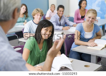 Group Of High School Students Listening To Teacher In Classroom