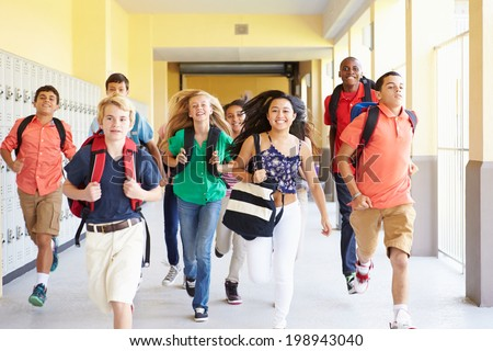 Group Of High School Students Running Along Corridor
