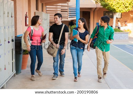 Group of high school students talking and laughing in a hallway between classes