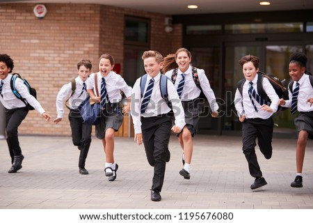 Group Of High School Students Wearing Uniform Running Out Of School Buildings Towards Camera At The End Of Class Stockfoto ©