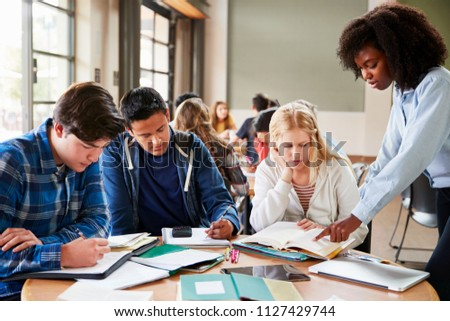 Group Of High School Students With Female Teacher Working At Desk