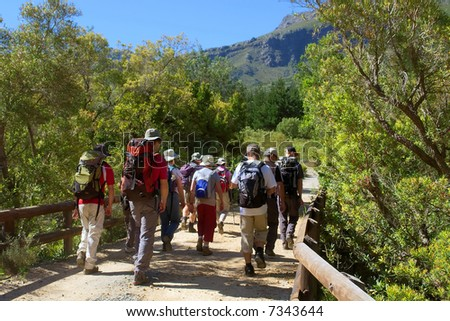 Group of hikers crosses the bridge - and majestic mountain landscape as a background. Shot in Jonkershoek nature reserve, Stellenbosch, Western Cape, South Africa.