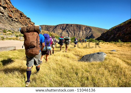 Group of hikers crosses wheat field - and awesome mountain landscape as a background. Shot in the Langeberge highlands near Grootrivier, Garden Route, Western Cape, South Africa.