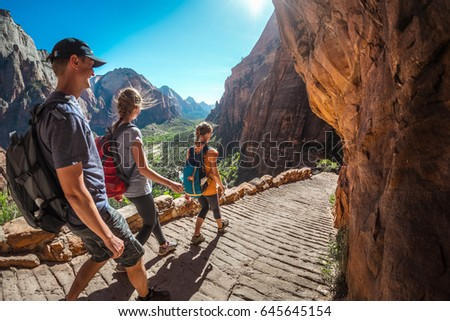 Group of hikers friends walking down the stairs and enjoying view of Zion National Park, USA