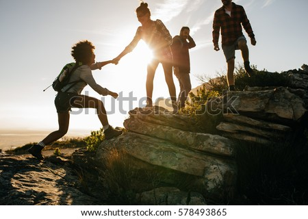 Shutterstock Group of hikers on a mountain. Woman helping her friend to climb a rock. Young people on mountain hike at sunset.