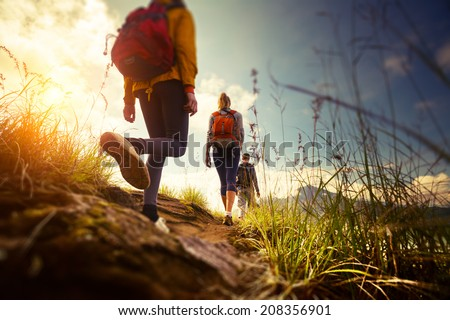 Shutterstock Group of hikers walking in mountains. Edges of the image are blurred