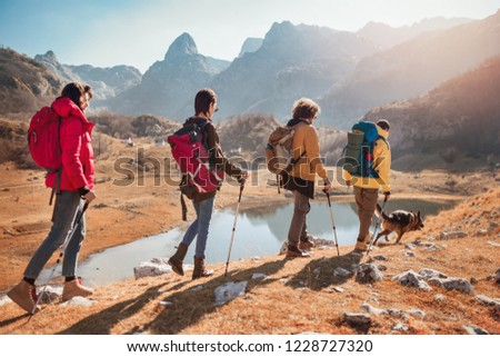 Group of hikers walking on a mountain at autumn day near the lake. #1228727320