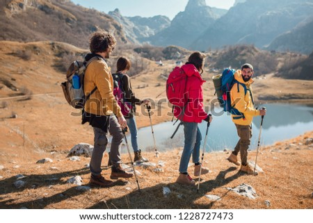 Group of hikers walking on a mountain at autumn day near the lake. #1228727473