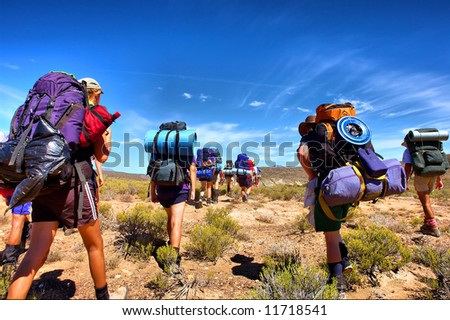 Group of hikers walks in savanna - low-angle view. Shot in the Langeberge highlands near Grootrivier and Gouritsrivier rivers crossing, Garden Route, Western Cape, South Africa.