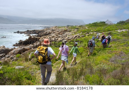 Group of hikers walks on sea beach to mountains. Shot near Strand, Pringle and Betties Bays, Western Cape, South Africa.