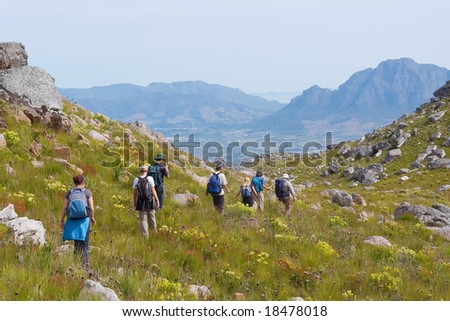 Group of hikers walks through valley - and misty mountain landscape as background. Shot in Klein Drakenstein Mountains, near Paarl, Western Cape, South Africa.
