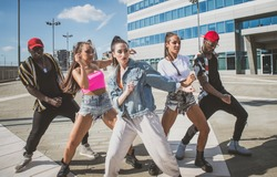 Group of hip hop dancers permorming their dance. Crew making show in an urban place