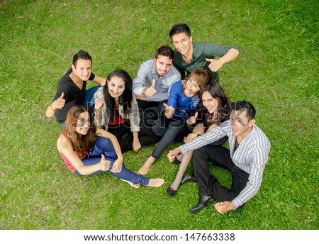 Group of hispanic teens thumbing up outdoors