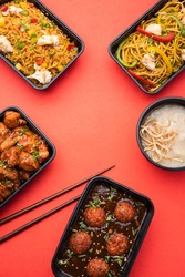 Group of home delivered Indo Chinese food in plastic packages, containersor boxes containingschezwan noodles, fried rice, chilli chicken, manchurian and soup. Online food ordering concept in India