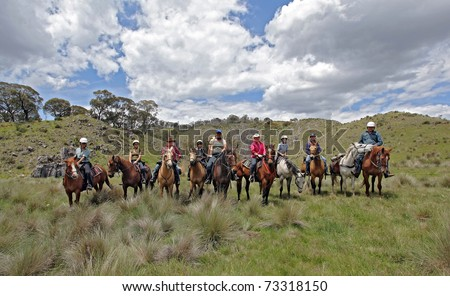 group of horse riders having fun in the mountains - stock photo
