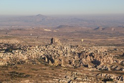 Group of hot air balloons flying over ancient stone city in Cappadocia