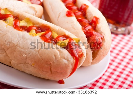 group of hot dogs and drink on checked table-cloth table - stock photo