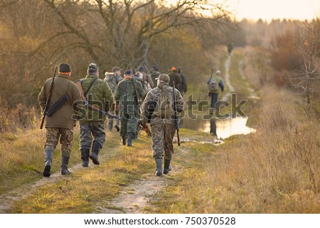Group of hunters during hunting in forest. chase hunting. Hunter with weapon. Hunter with friends. Hunters walking in the forest. hunters on hunting in the fall. hunter at dawn.