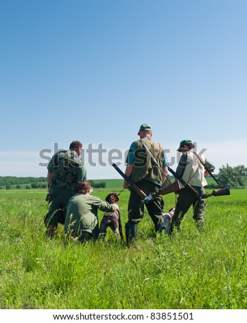 group of hunters with their dogs looking into the distance