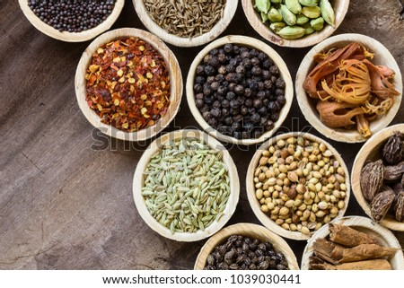 Group of indian spices in coconut bowls on wooden background. Cumin, chili, black pepper, mace, cardamom, anise, coriander, fennel, cinnamon; papaya seeds #1039030441
