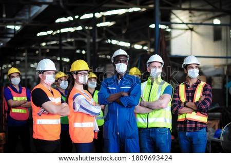Group of industrial worker team consist of Technicians, Engineer, factory Manager wearing helmet and surgical mask to protect Coronavirus, Covid-19 inflection and safety working in manufacturing plant Photo stock ©