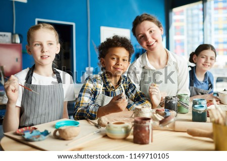 Group of intercultural pupils and their teacher in aprons sitting by wooden table in studio of arts and crafts and painting #1149710105