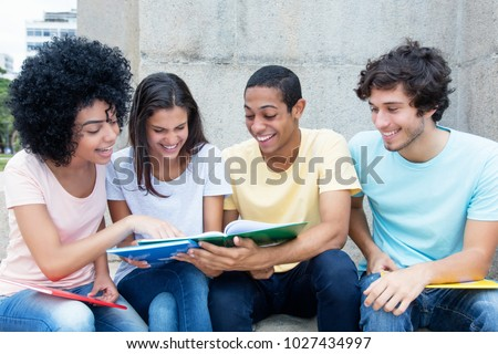 Group of international students learning outdoors on campus in summer