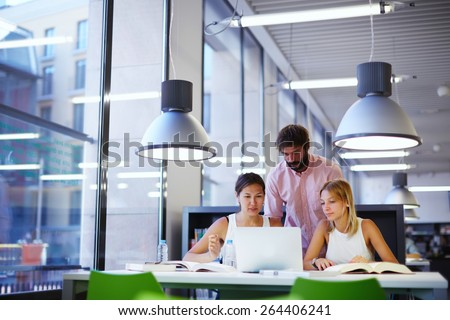 Group of international university students learning in library, three colleagues of modern work co-working space talking and smiling while sitting at the desk with laptop computer, exam preparation