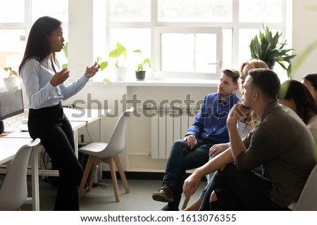 Group of interns or corporate staff young and older professionals seated on chairs in co-working space listening African ethnicity business trainer, gain new knowledge in, corporate training concept Photo stock ©