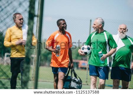 group of interracial elderly sportsmen with sportive water bottles walking on football field
