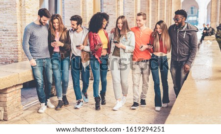 group of interracial friends meeting in the city center. they are having fun with smart phones and social media, walking together and chatting together