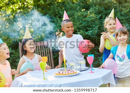 Group of interracial kids celebrate friend's birthday with tablefireworks